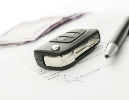 An image that shows car keys, money and a pen.