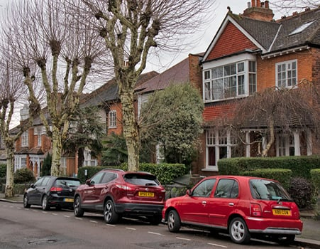 Cars parked in front of a row of houses