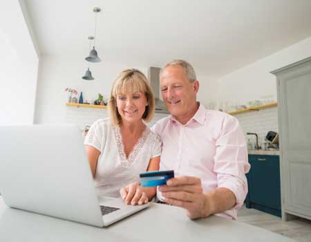 couple looking at a laptop holding a debit card