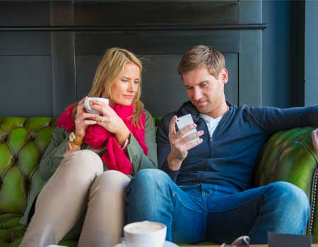 couple sat looking at a smart phone