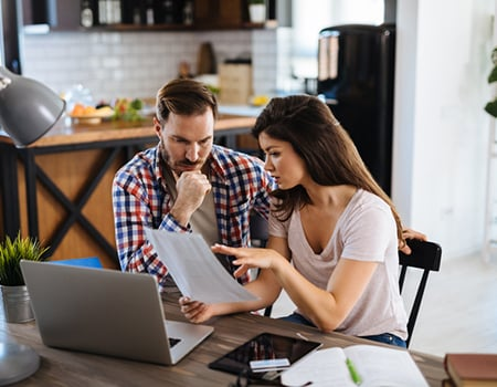 Couple sat at their dining room table looking at loans online using a laptop