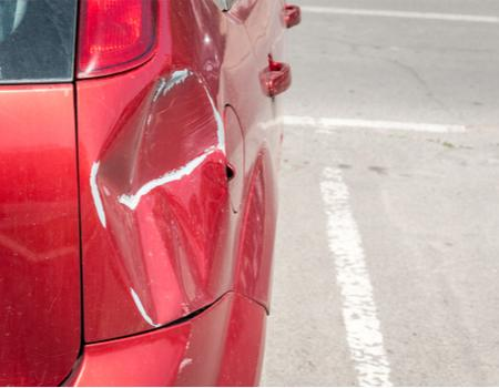A parked dented red car
