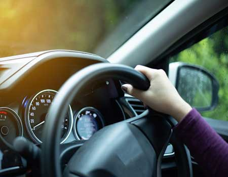 persons hand on steering wheel driving