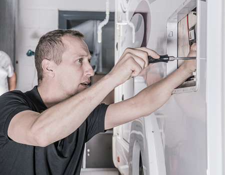 Technician with Screwdriver Looking For Potential Issues Inside Outside Camper Compartment