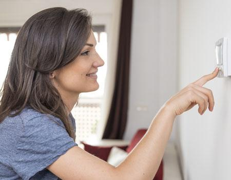 Lady checking thermostat