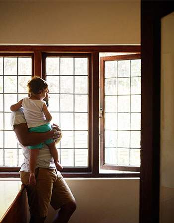 father and child looking out of window in new home