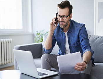 A man looking at his laptop on the phone | Compare the Market