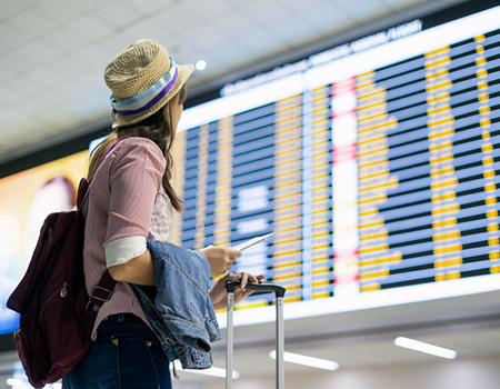A young woman looking for details of her flight in the airport