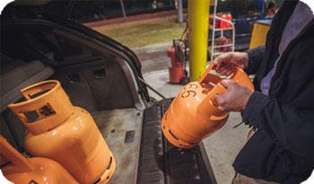 An individual lifting a gas can | Compare the Market