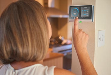 An individual looking at their smart meter