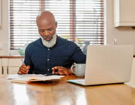 man going over his finances and paperwork at home