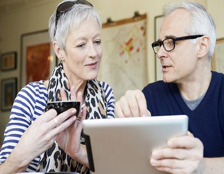A mature man and woman in a cafe with a digital tablet