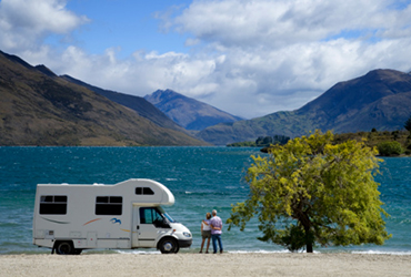 A couple standing next to their motorhome looking at a view of the mountains