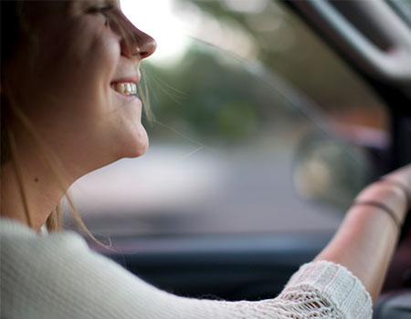Young woman smiling whilst driving