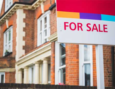For sale sign displayed outside a terraced house