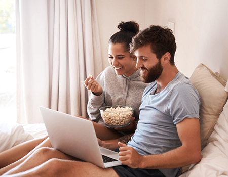 couple using a laptop to stream a film whilst eating popcorn and relaxing on the bed
