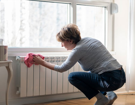 woman cleaning radiator at home