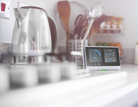 An image of a smart meter by a kettle.