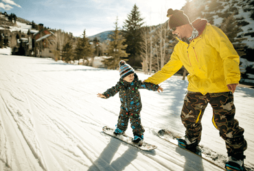 A father and son snowboarding together.
