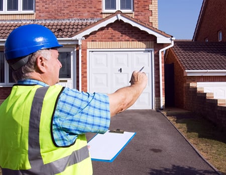 A property surveyor wearing high vis is looking at a house taking notes on a clipboard
