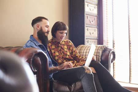 Two individuals sitting on the sofa and comparing new broadband providers