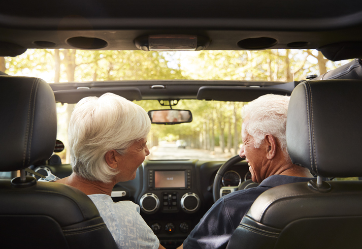 An older couple trying out a new car.
