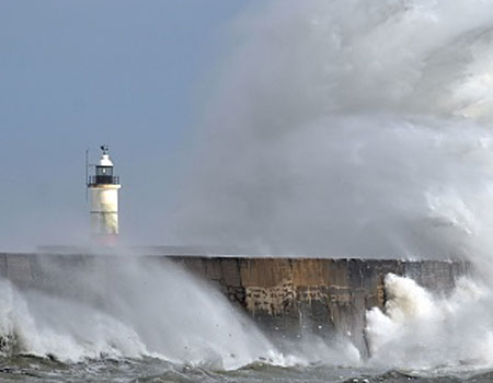A picture of waves crashing against a harbour wall