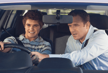 A father providing his son with some driving tips.