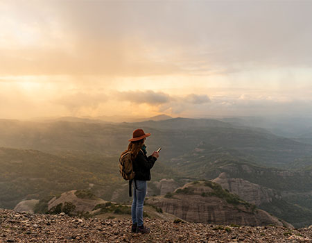 Person standing at mountain summit taking picture of view