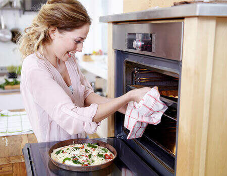 A lady using her oven more efficiently, by cooking multiple things together.
