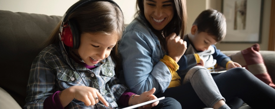 Image of a mother and two children looking at their iPads