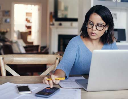 Woman doing monthly budget on laptop
