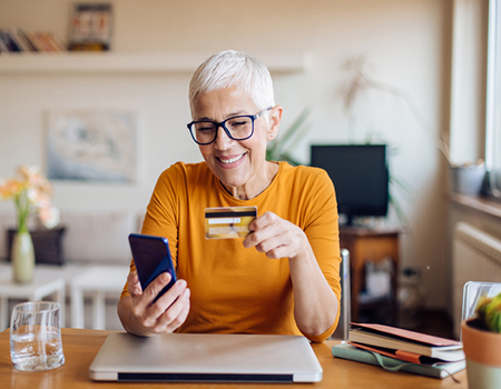 woman banking from her home office using mobile phone